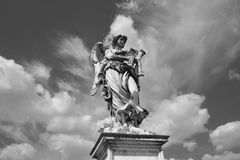 Angel in Rome. Angel statue with scourge on Castel Sant`Angelo Bridge, with heavenly sky Black and White Royalty Free Stock Image