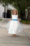 Angel runs through garden. Angelic child with blonde ringlets holds her gown and runs down a garden path.  She is wearing a white gown with bright blue sash Royalty Free Stock Images