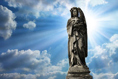 An angel sculpture with clouds beckground Royalty Free Stock Photo