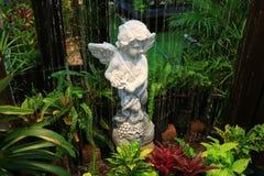 Angel Sculpture de pedra branco na fonte do jardim entre muitas plantas verdes e vermelhas foto de stock