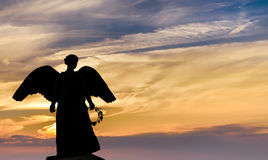 Angel sculpture on sunset background Stock Images