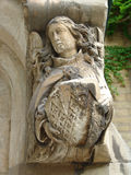 Angel with shield on door archway. Stone carving of angel on doorarch bearing shield royalty free stock photo