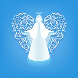 Angel silhouette with ornaments wings. Angel with ornamental floral white wings ang glowing nimbus on a blue background.  Beautiful applique. Abstract design Stock Photography