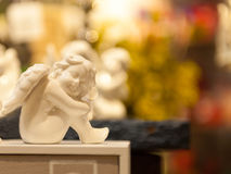 Angel sitting seat on the box porcelain figurine Royalty Free Stock Photos