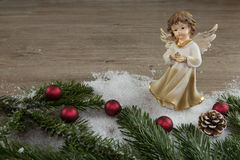 Angel in the snow and red christmas balls Royalty Free Stock Photography