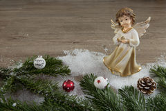 Angel in the snow and red christmas balls Royalty Free Stock Images