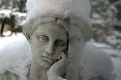 Angel with snow thinking about dead with reflection. 