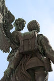 Angel and soldier statue. Statue of angel carrying soldier to heaven against simple blue sky Royalty Free Stock Images