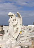 Angel in sorrow on cemetery. SAN JUAN, PUERTO RICO - MARCH 14, 2015: The statue in white marble of a human-sized angel with wings. She is sad and in sorrow Royalty Free Stock Photos