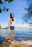 Angel standing by the sea. Woman with angel wings standing by the sea happily stock photo