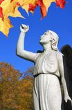 Angel statue in cemetary with raised arm and leaves Royalty Free Stock Photos