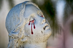 Angel statue on cemetery crying blood tears Stock Images