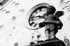 Angel statue with church in background. Statue of little angel in front of old church in black and white Stock Images