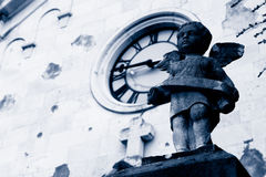 Angel statue with church in background. Statue of little angel in front of old church. Dual tone image Royalty Free Stock Images
