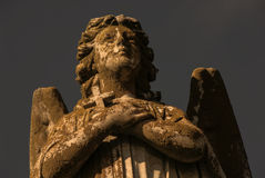 Angel Statue With Cross. A statue of a male angel with wings holding a small cross Royalty Free Stock Image