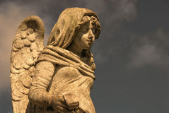 Angel Statue With Cross. A stone statue of a male angel with wings, holding a cross Royalty Free Stock Photos