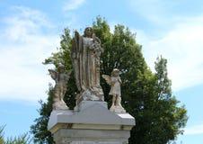 Angel Statue door kinderen wordt omringd dat Stock Foto