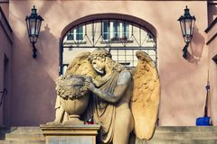 Angel statue in front of gate on Malostransky cemetery, Prague. Angel statue with urn and laurel wreath in front of gate on Malostransky cemetery, Prague, Czech Stock Images