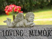 Angel statue on gravestone. A small statue of an angel resting on top of a gray marble tombstone in a cemetery Stock Image
