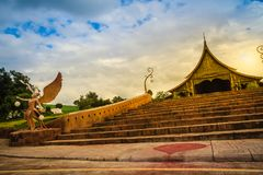 An angel statue holding sphere lamps under cloudy blue sky day i. N front of the Buddhist church in Wat Sirindhorn Wararam Phu Prao, public temple in Ubon Royalty Free Stock Photography