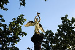 Angel statue with pigeon. Photo golden statue of an angel with a dove in his hands on a pedestal in the form of a column on a background of blue sky and foliage Stock Photos
