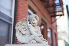 Angel statue on a porch in New York City. A peaceful white angel statue is sitting on a porch in New York City in front of a red brick stone building Stock Photography
