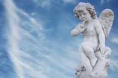 Angel with streaky sky. Angel with blue streaky sky behind him stock photos