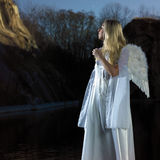 Angel in sun set by the lake Stock Photos