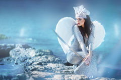 Angel with sword. Beautiful girl in a brilliant dress at the seaside Stock Photo