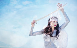 Angel with sword. Beautiful girl in a brilliant dress at the seaside Royalty Free Stock Images