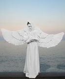 Angel - symbol of love, purity and protection. A girl in a white dress with wings on background of the sea.Angel - symbol of love, purity and protection Royalty Free Stock Images