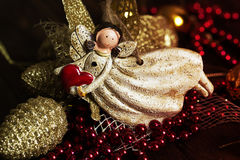 Angel toy with a heart in hand on a Christmas background. Christ Stock Photos