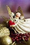 Angel toy with a heart in hand on a Christmas background. Christ Stock Image