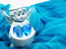 Angel toy holding crystal heart in hands on silky background Stock Photos