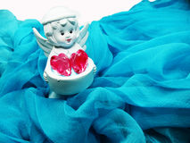 Angel toy holding crystal heart in hands on silky background Stock Image
