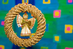 Angel toy made of straw. Hanging against colorful background Royalty Free Stock Image