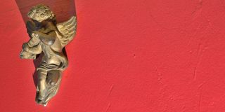 Angel on a vivid red wall Royalty Free Stock Photo