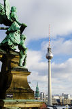 Angel watching the Fernsehturm. Statue at the top of berlin cathedral, watching over berlins television tower Royalty Free Stock Images