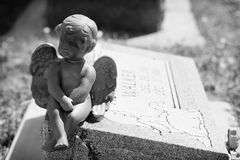 Angel Watching Over You. Statue of baby angel sitting on a grave royalty free stock photos