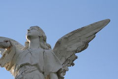 Angel. A weathered Angel gazes at the late afternoon sun against a cloudless blue sky Royalty Free Stock Image