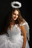 Angel in white against dark Royalty Free Stock Image