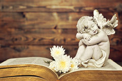 Angel and white flowers on old book. Wooden background Royalty Free Stock Images