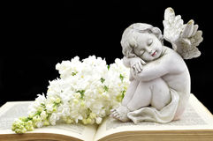 Angel and white spring flowers. On the old book Royalty Free Stock Photo