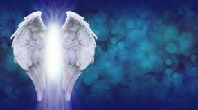 Angel Wings on Blue Bokeh Banner. Wide blue bokeh background with a large pair of Angel Wings on the left side and a shaft of bright light between royalty free stock photography