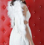 Angel girl wings on back in white dress on red background royalty free stock photography