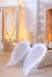 Angel Wings que miente en cesta cerca de la chimenea Foto de archivo