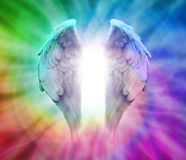 Angel Wings on Rainbow Spiral Background. Angel Wings on spiraling Rainbow colored Background with white energy between wings Royalty Free Stock Images