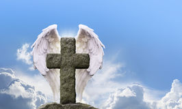 Angel Wings and Rustic Cross. Highly detailed Angel Wings either side of a rustic stone cross with a bright sunny blue sky background and fluffy clouds behind Royalty Free Stock Image