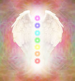 Angel Wings and Seven Chakras. Bright Angel wings and seven chakras on colorful wispy background with light coming from between wings Stock Illustration