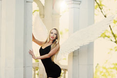 Angel with wings. Angel with white wings near the arch royalty free stock image
